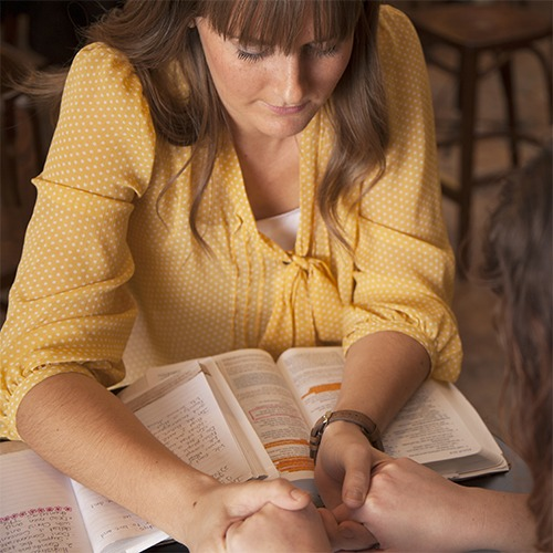 Our History | Freedom House |  woman praying over Bible